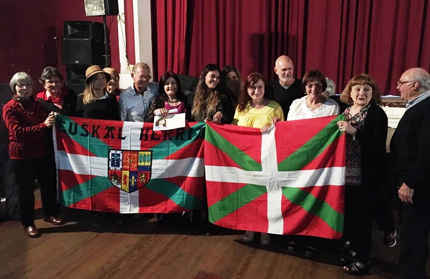 Monica Arrazubieta behind the Ikurriña with certificate in hand, surrounded by family and friends who attended the event