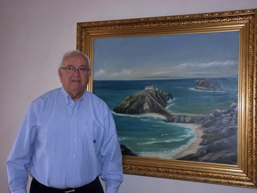 El vasco-chileno Luis Archibaldo Uriarte, de padre bakiotarra, frente a un cuadro de San Juan de Gaztelugatxe (foto EuskalKultura.com)