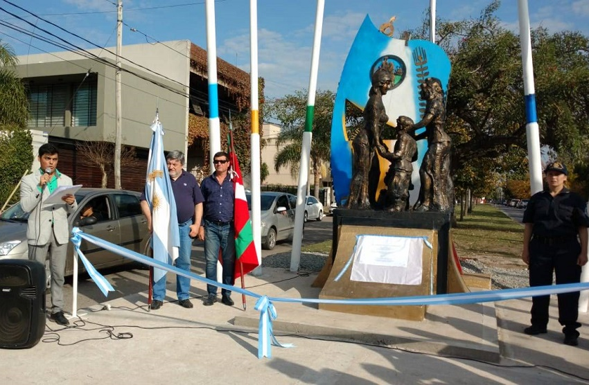 Raul Taretto and Juan Itcea pose representing the Basque community next to the monument to immigrants in Gral. Rodriguez