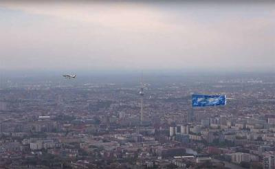 The airplane and banner with the skies of Gernika flying over Alexanderplatz, the epicenter of the German capital