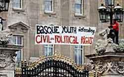 Los jóvenes sitúan la pancarta sobre la verja